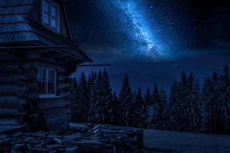 Milky way and rural cottage in the mountains at night Imagens