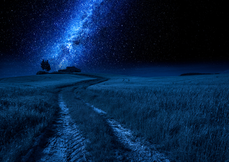 Milky way, country road and field at night, Tuscany