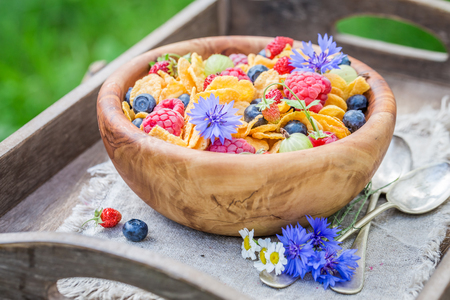 Closeup of cornflakes with berry fruits in wooden bowl Фото со стока