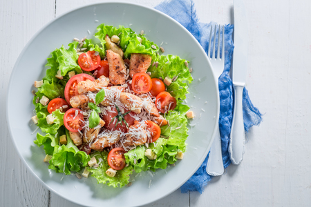 Top view of Caesar salad with chicken, tomatoes and cheese Фото со стока