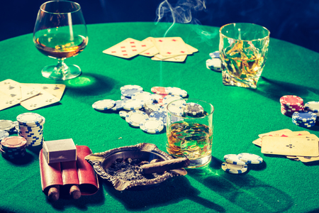 Green gambling table with whiskey, cigar and cards