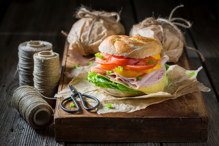 Homemade take away sandwich packed in a gray paper 写真素材