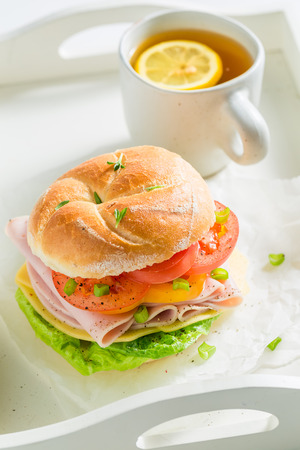 Tasty sandwich with vegetables, ham and tea Banco de Imagens
