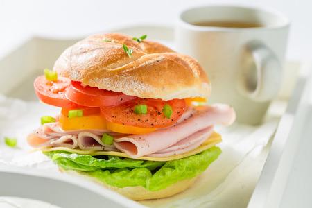 Crisp sandwich with ham, cheese, tomatoes and tea 写真素材