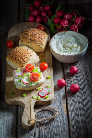 Tasty sandwich with radish, creamy cheese and tomatoes