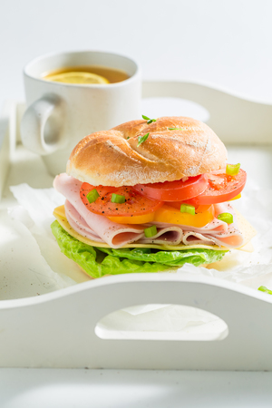 Delicious sandwich with fresh ingredients and tea