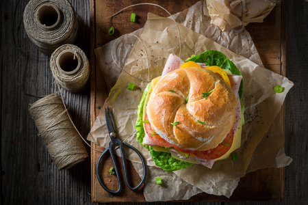Delicious take away sandwich with ham, cheese and tomatoes