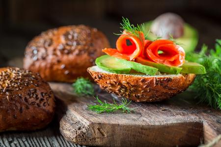 Fresh bun with avocado, dill and salmon
