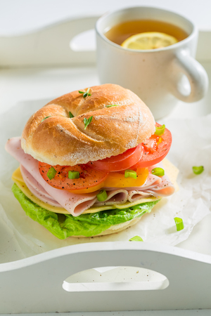 Crisp sandwich with tomatoes, cheesem, ham and tea