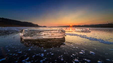 Beautiful frozen winter lake with piece of ice at sunset