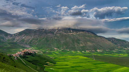 Cloudy sunset in the mountains over Castelluccio, Italy