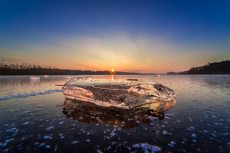 Cold piece of ice on frozen lake at dawn Stock fotó