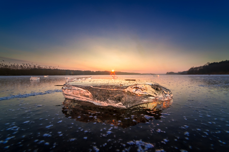 Cold piece of ice on frozen lake at sunset