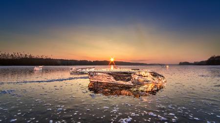 Stunning piece of ice on frozen lake at sunset Фото со стока - 97371286