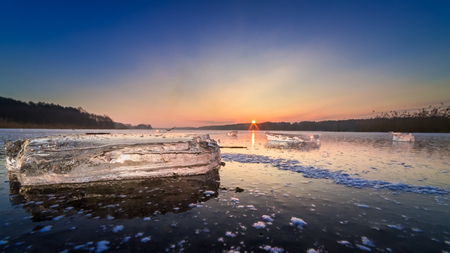 Beautiful frozen winter lake with piece of ice at dawn