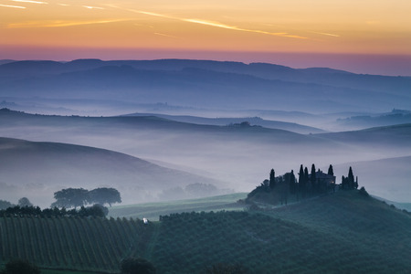 Stunning foggy fields at dawn in Tuscany, Italy