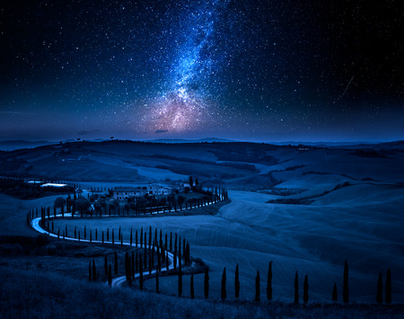 Milky way and winding road with cypresses, Tuscany
