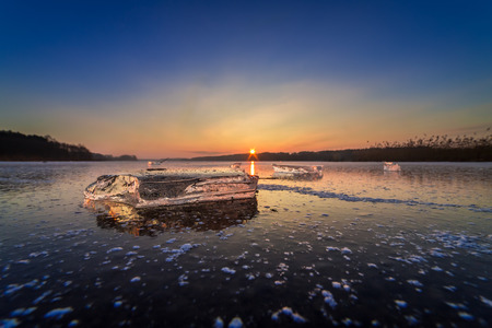 Cold frozen winter lake with piece of ice at dawn