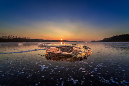 Cold frozen winter lake with piece of ice at sunset