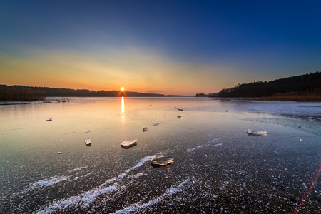 Beautiful piece of ice on frozen lake at dawn