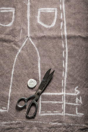 Drawing with white chalk a tailors project of trousers