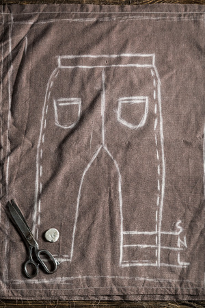 Tailor draft of trousers with scissors and chalk Stock Photo