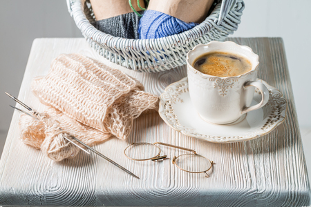 Closeup of knitted scarf with color skein and coffee 스톡 콘텐츠
