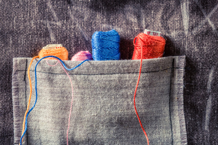 Colored threads in small pocket in tailor workshop Stock Photo