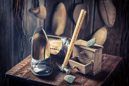 Aged shoemaker workplace with shoes, hammer and nails