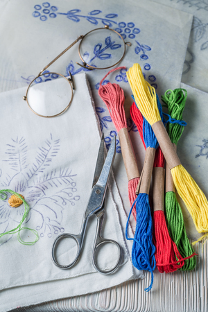 Closeup of colored threads and embroidered napkins