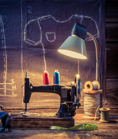Old sewing workshop with color threads, machine and material Stock Photo