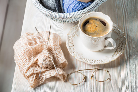 Coffee cup and knitted scarf and color skein