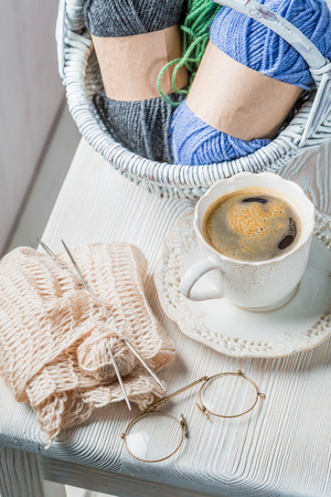Cup of coffee and knitting a white scarf
