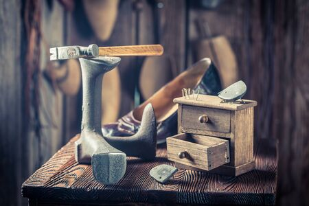 Vintage shoemaker workplace with hammer, nails and shoes