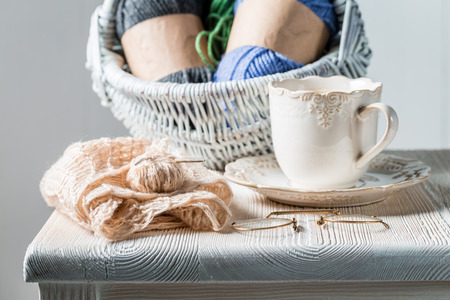 White knitted scarf with color skein and coffee