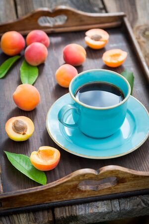 Fresh coffee and plums on wooden tray