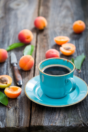 Blue coffee and orange plums in summer garden