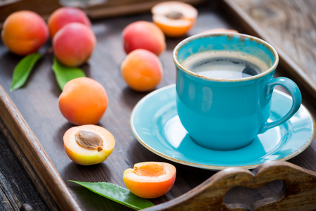 Fresh coffee and plums in summer garden