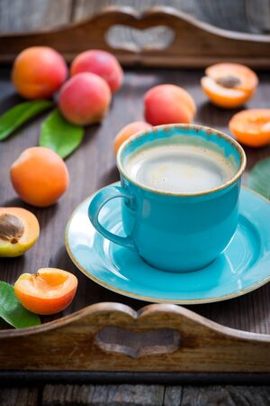Delicious coffee and plums on wooden tray