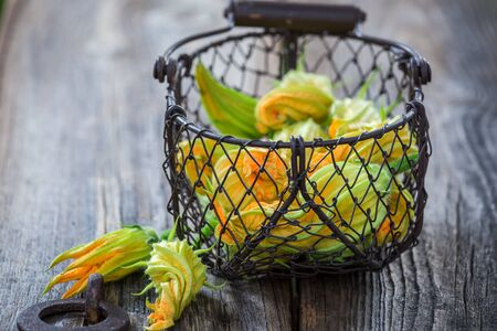 Fresh and green zucchini flowers in old basket