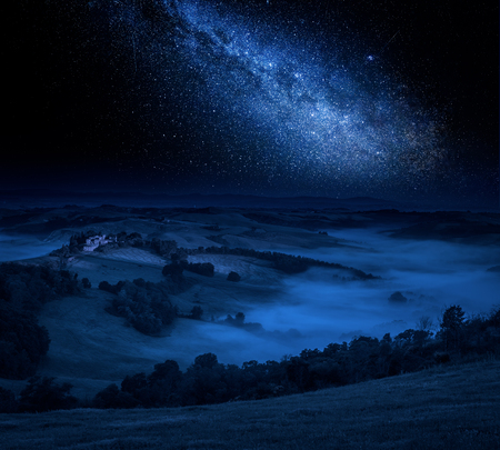 Milky way and foggy valley in Italy Stock Photo