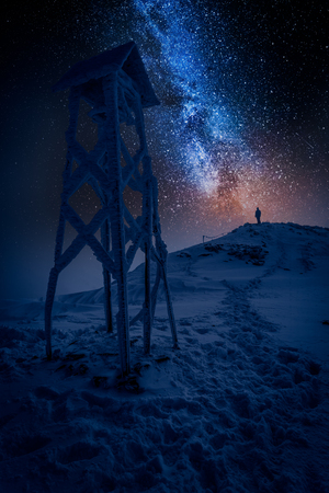 Man looking from mountain to the milky way in winter Stock Photo
