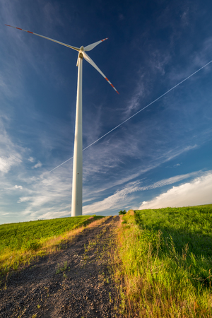 Wind turbines as alternative on green field and blue sky