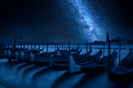 Milky way and swinging gondolas at night, Venice, Italy Фото со стока