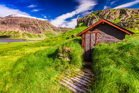 Small mountain hut on green grassy hill, Iceland
