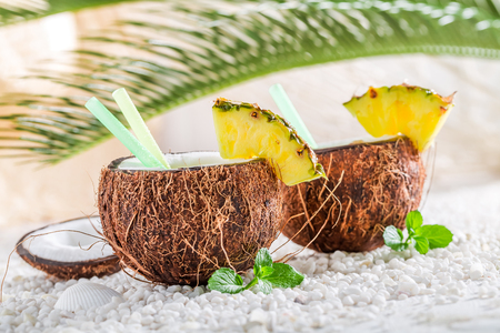 Sweet pinacolada in coconut on white pebbles