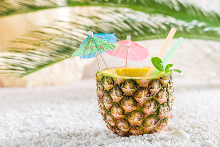 Fresh drink in pineapple with cocktail umbrellas on white pebbles