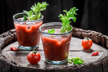 Bloody mary cocktail with tomatoes and celery on old barrel