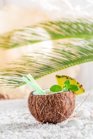 Tasty pinacolada in coconut in sunny day on white pebbles