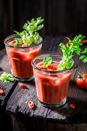 Cold bloody mary cocktail with tomatoes on wooden table Stock Photo